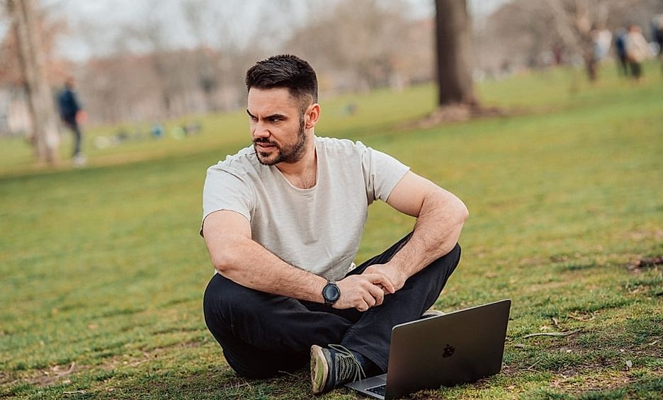 man sitting on the grass with laptop